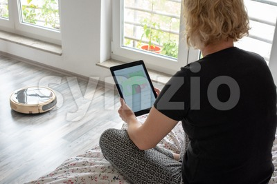 Woman is steering her vacuum cleaning robot from the bed Stock Photo