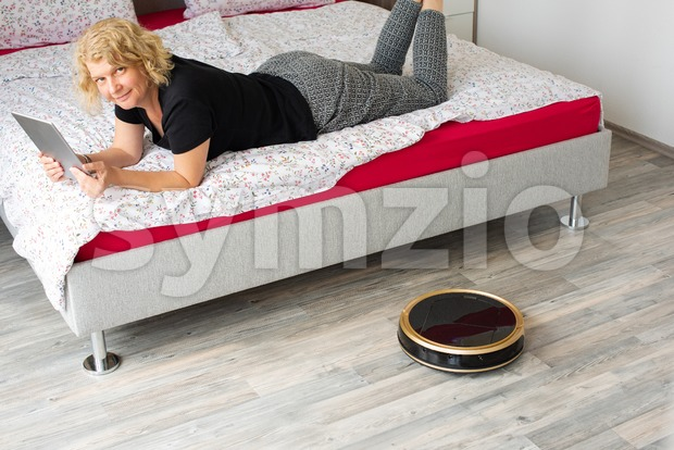 A middle aged woman is reading on her digital tablet on her bed while her vaccum cleaning robot is cleaning ...