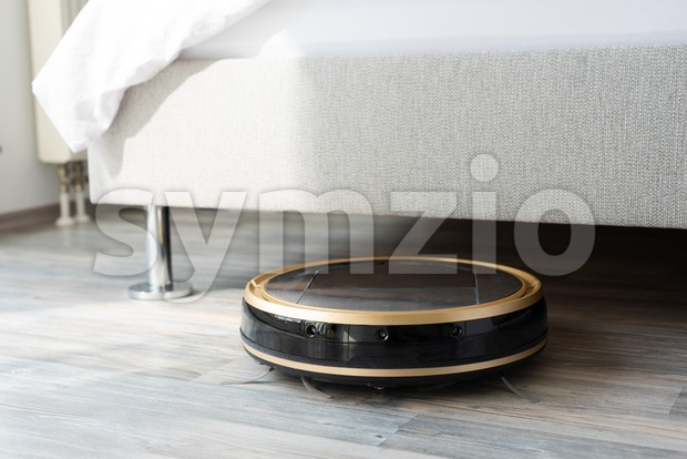 Robot vacuum cleaner runs under bed Stock Photo