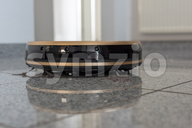 Modern autonomous robotic vacuum cleaner on bright marble floor with reflections. Focus on hairs and dust. with sace for your ...