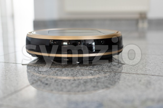 Robotic vacuum cleaner on bright marble floor Stock Photo