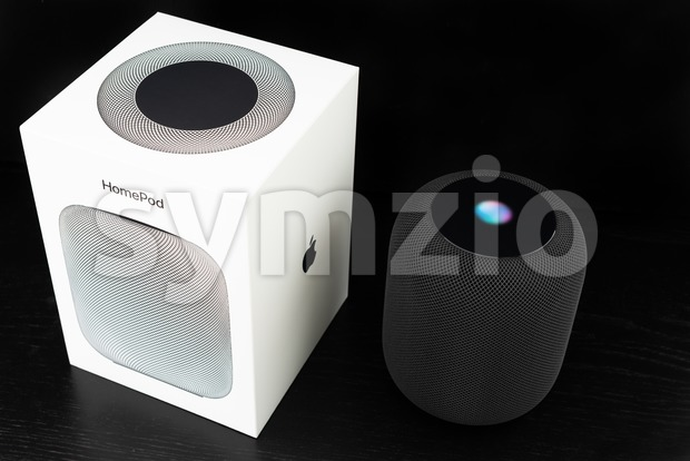 Ostfildern, Germany - June 26, 2018: Unboxing an Apple HomePod speaker: The speaker is standing next to its iconic box, ...