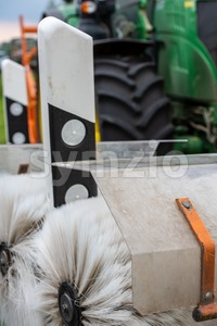 Tractor cleaning reflector posts Stock Photo
