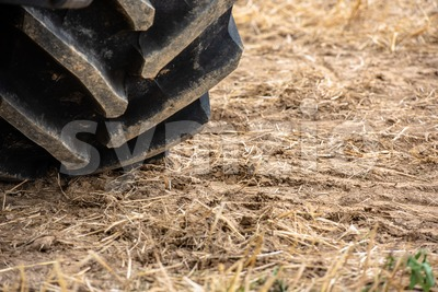 Wheels of tractor plowing field Stock Photo