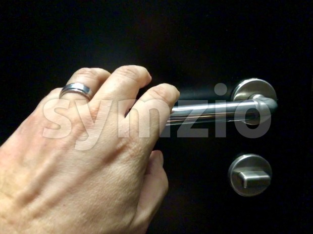 Closeup of male hand approaching silver door knob to open or close the black door of a toilet from the ...