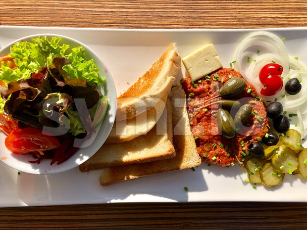 Steak tartare served with capers, pickled cucumbers and chopped onion with toast bread and a salad on a white plate