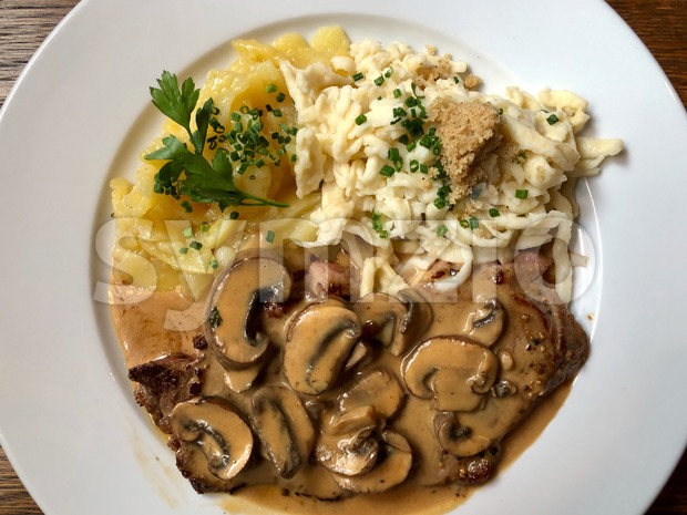 Swabian speciality: Escalope chasseur with spaetzle, mushroom sauce and potato salad