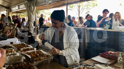 People are enjoying delicious food at a Neighbourgoods Market at the waterfront of Cape Town, South Africa. Stock Photo