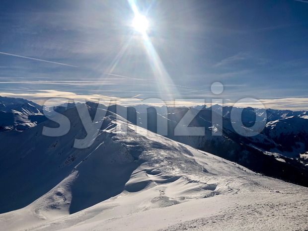 Mountain panorama of the Austrian ski resort of Saalbach-Hinterglemm , Austria with beautiful sunlight against a great blue sky.