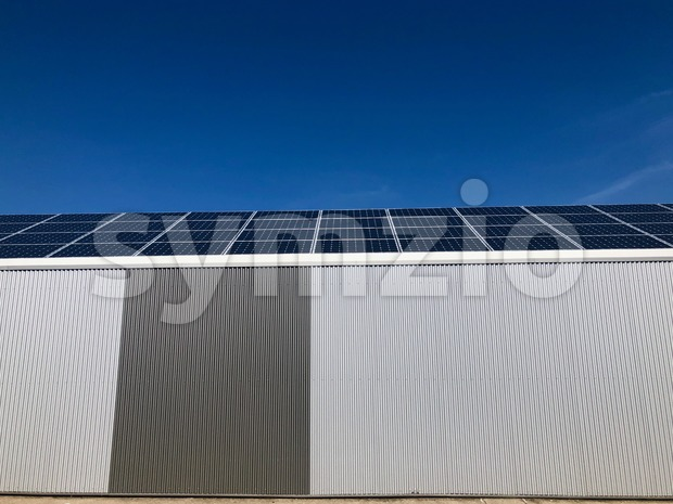 Sustainability: A modern iron warehouse covered by solar panels against great blue sky