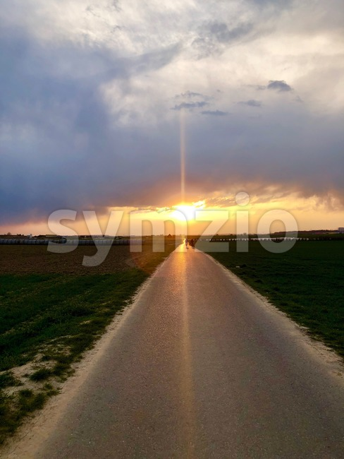 Nature landscape of sunset light above asphalt road with cyclists at the horizon