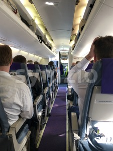 Interior of airplane with passengers on seats waiting for take off Stock Photo