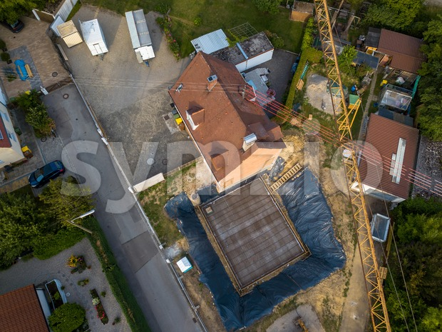 Aerial view of a construction site within a village in Germany. Looking straight down with a satellite image style, the ...
