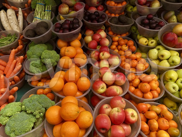 Fruit market with various colorful fresh fruits and vegetables sold in plastic buckets in Birmingham, Great Britain