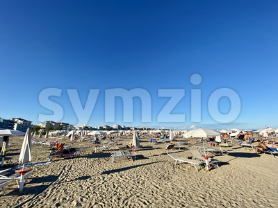 Unidentifiable people in the late afternoon on Caorle beach in Veneto, Italy Stock Photo