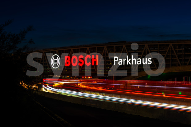Huge Bosch letters at the Stuttgart Airport parking garage with long exposure of highway A8 at dusk. Bosch is a German multinational engineering and Stock Photo