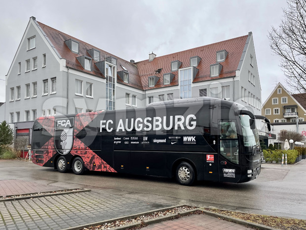 The team bus of football club FC Augsburg is waiting in front of the hotel where the team resides before their next match. Stock Photo