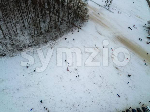 Aerial view of people enjoying a winter day by sledding on a small ski slope during winter holidays. The ski lift is not operating due to the Corona Stock Photo