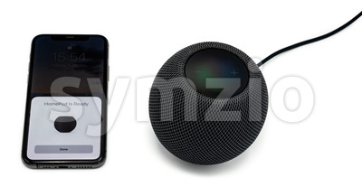 A black Apple Homepod Mini smart speaker is set up using an Apple iPhone 12, studio shot with shadows on a clear white background. Stock Photo