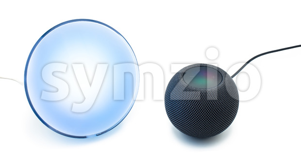 Siri, the voice control of the new black Apple Homepod Mini smart speaker, is use to control a Philips Hue smart home lamp on a clear white Stock Photo