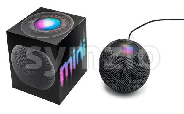 A black Apple Homepod Mini smart speaker next to its packaging on a clear white background. Stock Photo
