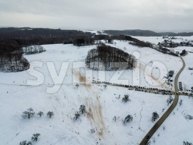 Aerial view of people enjoying a winter day by sledding on a small ski slope during winter holidays in a ...