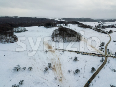 Aerial view of people enjoying a winter day by sledding on a small ski slope during winter holidays in a small village on the Swabian Alps in Southern Stock Photo