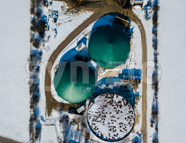 Aerial view on a biogas plant in snowy fields producing renewable energy from biomass in southern Germany on a bright winter day Stock Photo