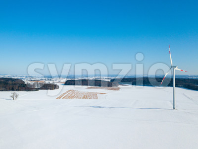 Aerial view of wind turbine in snow covered landscape in rural Germany on a sunny winter day with great blue sky and shadow visible on the snow Stock Photo