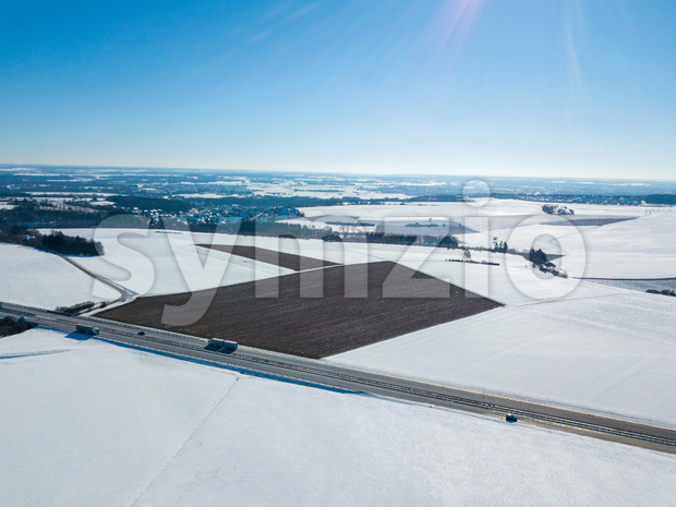 Aerial drone shot of a German Autobahn with cars driving next to snow covered fields on a sunny winter day- highway A8 near Ulm in Southern Germany Stock Photo