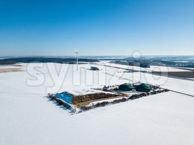 Aerial view on biogas plant and wind turbine in rural Germany in winter snow on a sunny day with great blue sky Stock Photo