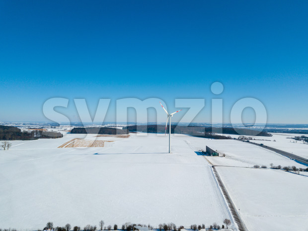 Aerial view of wind turbine in snow covered landscape next to highway A8 near Ulm in Southern Germany on a sunny winter day with great blue sky and Stock Photo