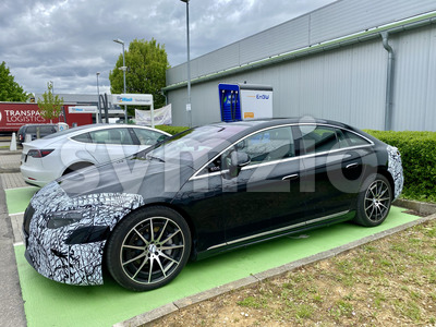 The new Mercedes EQS test car charges up with an EnBW supercharger at Ostfildern near Stuttgart in Germany. The car is wrapped in foil, the model is Stock Photo