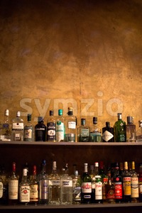 Bar shelves full of alcoholic beverages bottles Stock Photo