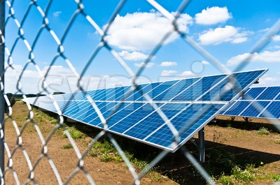 Solar panels behind fence Stock Photo