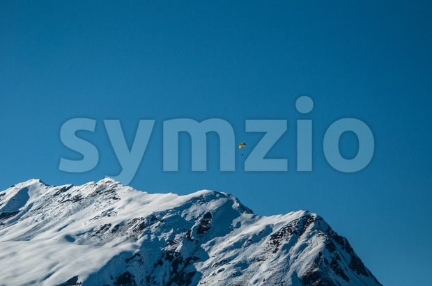 Beautiful winter mountain panorama with paraglider in Montafon, Austria