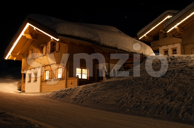 Wooden skiing huts covered with a lot of fresh snow at night in Montafon, Austria