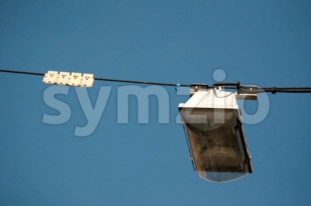 Street light hanging above a street with great blue sky