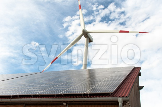 Barn covered with solar panels and wind turbine in the background