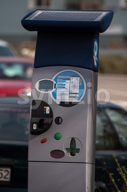 Modern solar powered pay parking machine with cars in the background