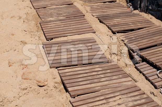 Weathered wooden boardwalk on sand Stock Photo