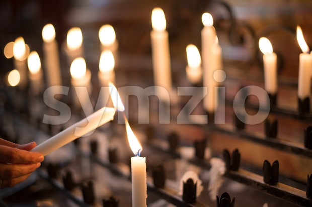 Woman lighting prayer candle Stock Photo