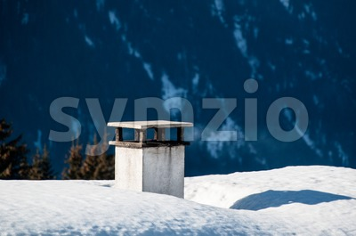 Chimney on snow covered roof Stock Photo