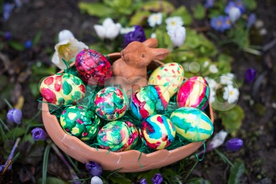 Easter basket amongst spring crocus flowers Stock Photo