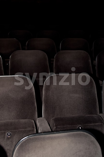 Empty chairs at cinema or theater. Gray toned