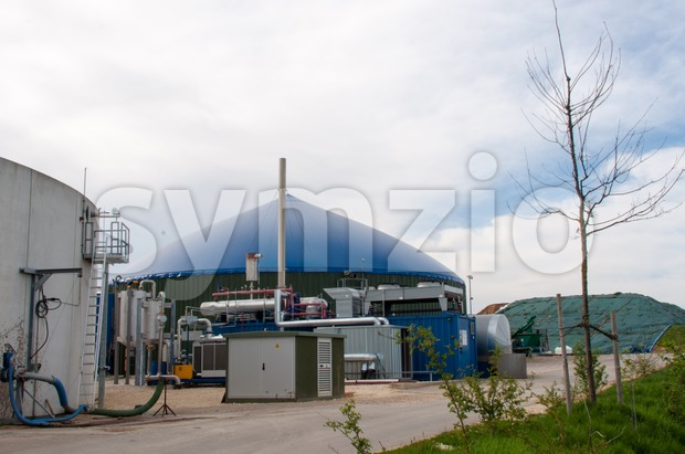 Different fermenters of a biogas plant in front of a cloudy blue sky