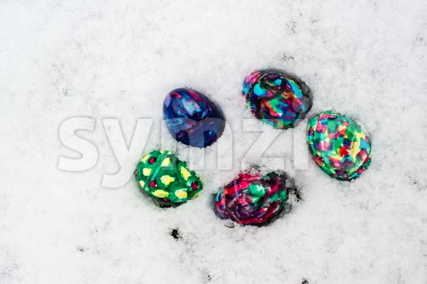 Colourful handpainted Easter Eggs in snow with space for your copytext