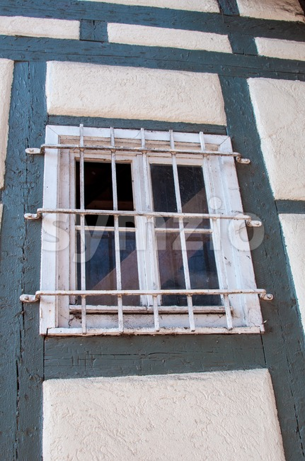 Old wooden framework facade of a half timbered house with barred window