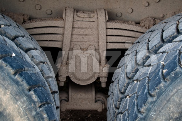Suspension detail of leaf-spring with tires of a dirty heavy truck