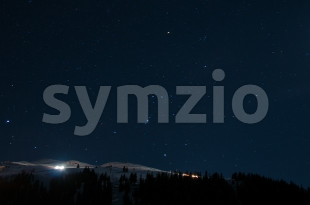 Night panorama of Montafon, Austria with great starry sky and snow groomer preparing the piste